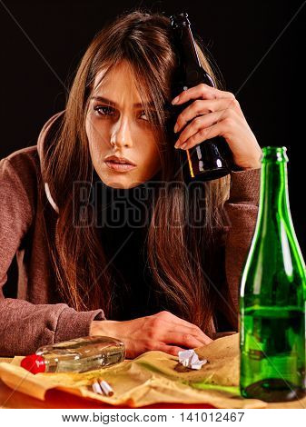 Girl in depression drinking alcohol and smokes cigarettes in solitude. Drinking habits. Girl is heavy drinkers on black background.