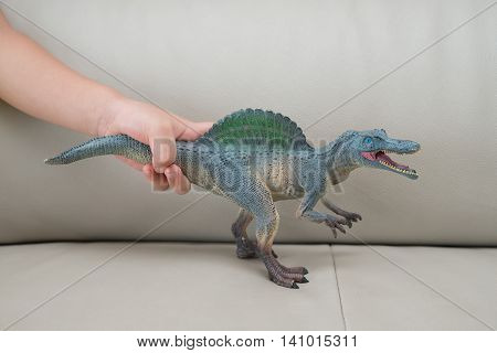 kids hand catching a greu spinosaurus toy on a sofa at home