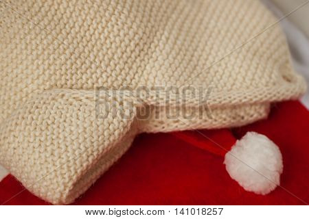 Knitted hat with ear-flaps on the background of Santa Claus xmas red hats