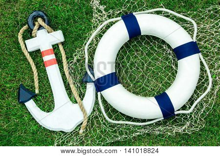 White anchor and lifebuoy on green lawn space for text