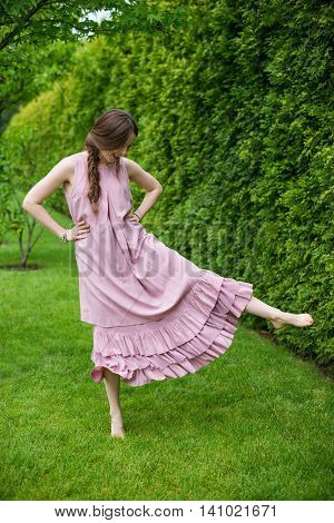 Young woman resting and having fun in the park dancing in long pink dress