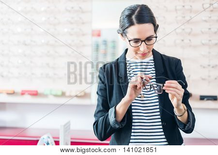 Woman taking glasses off shelf in optician shop