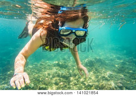 Woman snorkelling over floor of tropical sea in her summer vacation