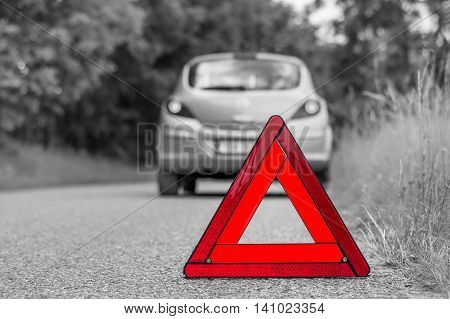 Red Warning Triangle And Broken Car On The Road