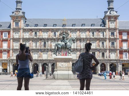 Madrid Spain - July 11 2016: Young women tourist taking pictures in Plaza Mayor square