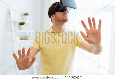 3d technology, virtual reality, gaming, entertainment and people concept - close up of happy young man with virtual reality headset or 3d glasses playing videogame at home
