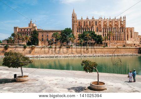 Palma de Mallorca Spain - May 27 2016: A couple of tourists looking at La Seu the gothic medieval cathedral of Palma de Mallorca and La Almudaina Royal Palace Spain. The Cathedral of Santa Maria