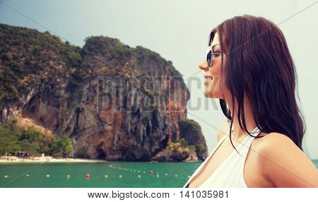 summer vacation, tourism, travel, holidays and people concept -face of smiling young woman in swimsuit with sunglasses over sea and island rock at tropical beach on bali background
