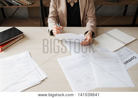 Unrecognizable woman reading document at her office desk, free space. Business woman working on paperwork, top view.