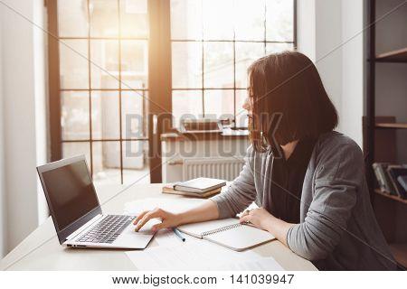 Beautiful woman surfing net at office on laptop. Uninteresting work, free time, break
