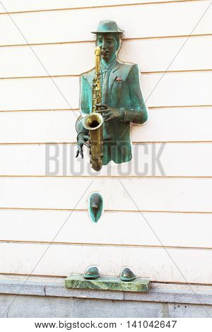 TBILISI, GEORGIA - SEPTEMBER 30, 2010 : Bronze statue of saxophonist coming through the wall on Rustaveli street in old Tbilisi, Georgia