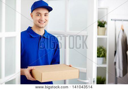 Portrait of deliveryman carrying a cardboard parcel box