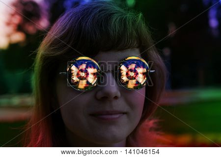 In the glasses of a young woman rides reflected in night illumination