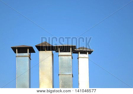 Four Galvanized Chimney Pipe Or Vent Pipe In A Row On Blue Sky Background