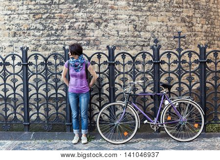 Young woman in purple shirt and purple vintage bicycle on the street in Prague Czech Republic