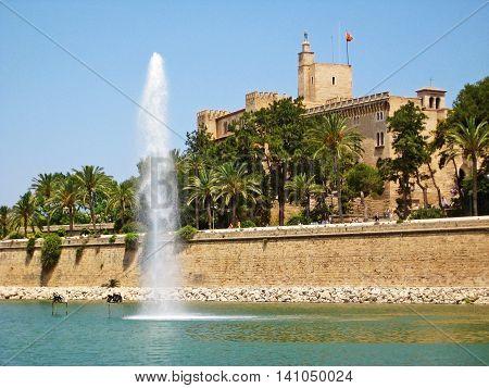 Palma de Majorca Spain - June 25 2008: Royal Palace of La Almudaina in Palma de Mallorca view from Parc de la Mar lake with fountain in front