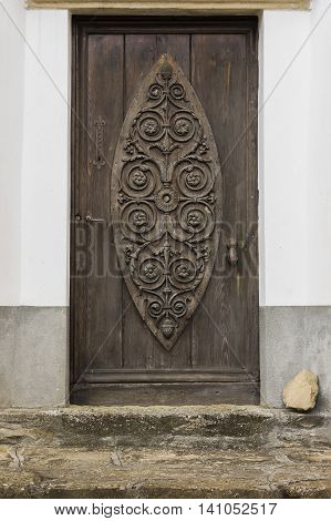 Old carved wooden and crooked door in Montechiaro d'Acqui Piedmonte Italy