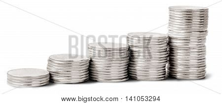 Progressively taller stacks of silver coins - isolated image