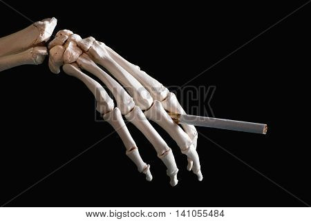 Skeleton hand holding cigarette close up image, horizontal