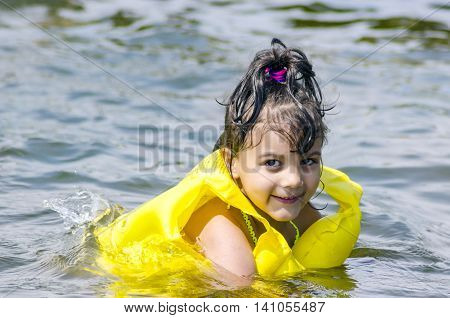 Five-year girl swims in the summer with a lifeline and vest in the sea