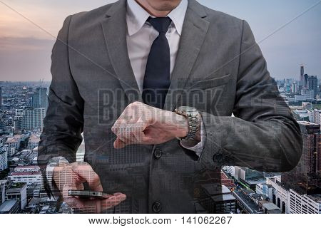 Double exposed of Businessman checking time on his wrist watch and holding mobile phone with cityscape.