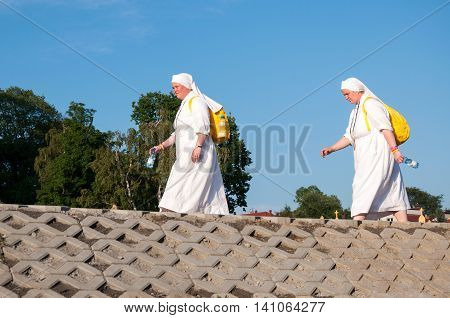 KRAKOW POLAND - JULY 29 2016: World Youth Day 2016. Two women female pilgrims nuns in white habits walking along the river embankment with yellow backpacks and bottles with water