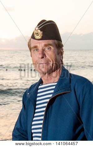 man standing in garrison cap and striped shirt on a background of sea summer day