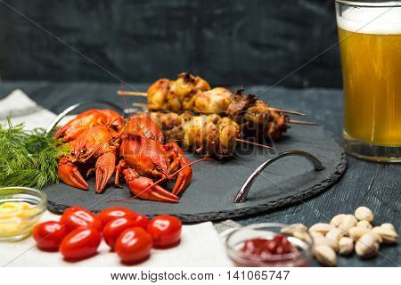 Tasty boiled crayfishes barbecueand and beer on wooden table with vegetables and sauce. snacks for drinks Concept