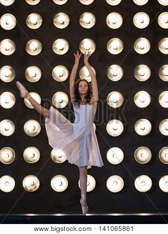 Dance. Ballet dancer is dancing in the dark hall with lamps. Yuong women ballerina exercising