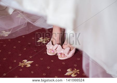 Pink Wedding shoes with bow on the feet of the bride in the white dress close up