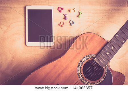 Top view of acoustic guitar with tablet touch computer gadget on wooden table background.vintage effect style picture