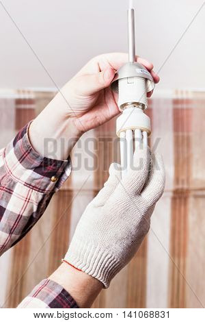 Electrician Changing Fluorescent Lamp In Holder