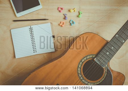 Top view of acoustic guitar with blank notebook on wooden table background.vintage effect style picture