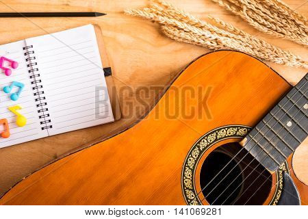 Top view of acoustic guitar with blank notebook on wooden table background.