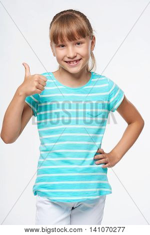 Smiling elementary school age girl standing gesturing thumb up sign, over white background
