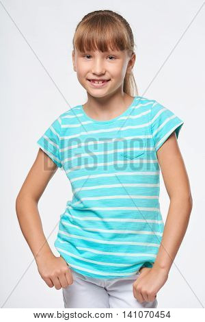 Smiling elementary school age girl standing relaxed with hands in pockets, over white background