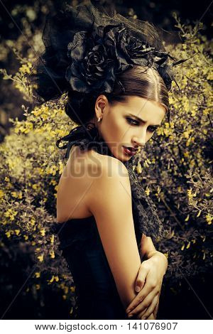 Beautiful brunette woman in long black dress and beautiful black headwear posing in the blossoming garden. Medieval, old times. Fashion. Gothic style. Sepia.