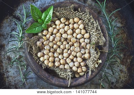 Garbanzo beans (chickpeas) with basil in clay bowl on metallic rustic background. Top view
