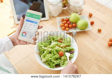 Woman checking nutrition information and calories on her phone when eating