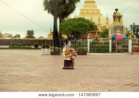 Lao women beautiful dressed in traditional dress nicely alms monks wait for surpluses moring time at Phra That Luang Vientiane Capital