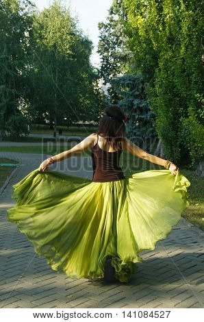 girl in a long green billowing skirt goes along the alley in the park