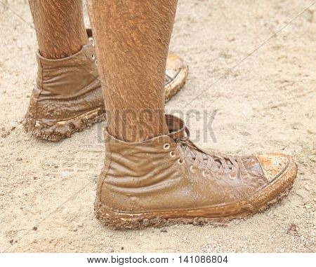 a pair of very muddy shoes and legs after running in a mud race