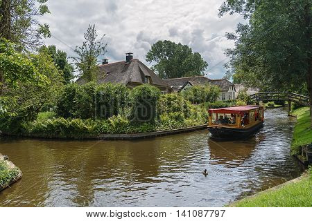 Giethoorn Netherlands - June 29 2016: known for its bridges waterways thatched cottages and punters. It is also called the 'Dutch Venice' and known to the world Monopoly edition.