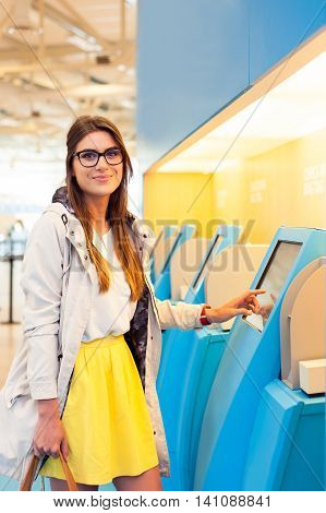 Young woman at self service transfer area doing self-check-in at automated machine with touchscreen display in airport terminal building
