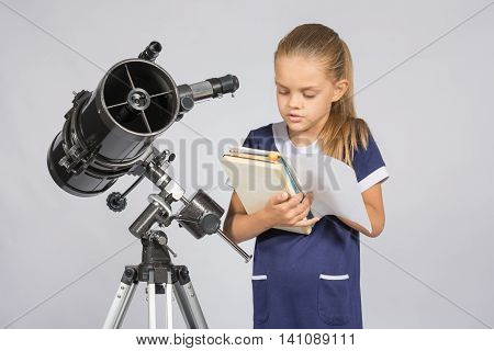 Schoolgirl Reading A Textbook While Standing Astronomer At The Telescope