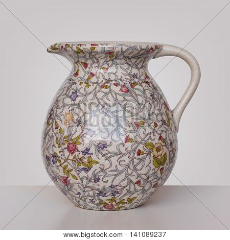 Storage for liquids - Old Vintage colored jug ewer on a light background.