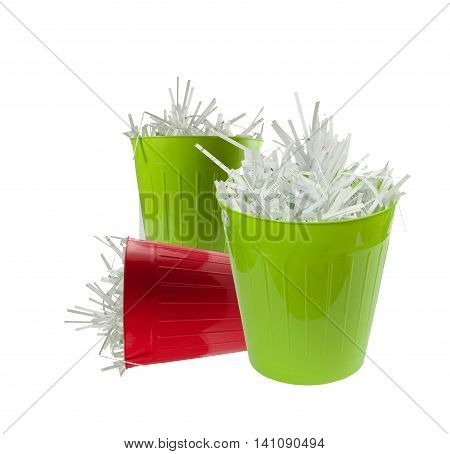 Two green and one red waste basket full with shredded paper