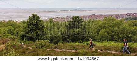 WEST KIRBY, ENGLAND, JUNE 26. A hilltop trail on June 26, 2016, overlooking West Kirby, England. A couple walks their dog on a hilltop trail overlooking West Kirby England.