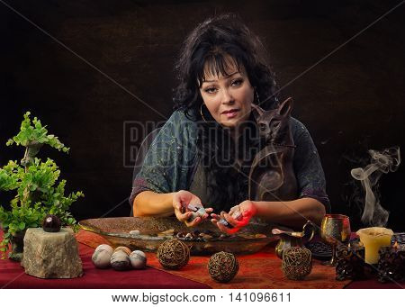 Gorgeous middle-aged female fortuneteller with cat statuette sitting at the desk. She holds some wet stones in hands and looks at camera. This clairvoyant predicts future by gemstones