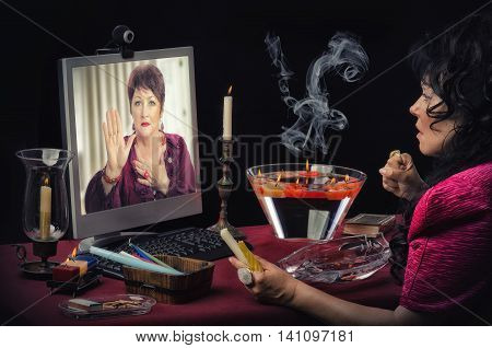 Fortuneteller is reading a clients right hand on the monitor online. Psychic looks at the shapes and lines of mature woman's palm tensely. Clients face looks a little bit scared